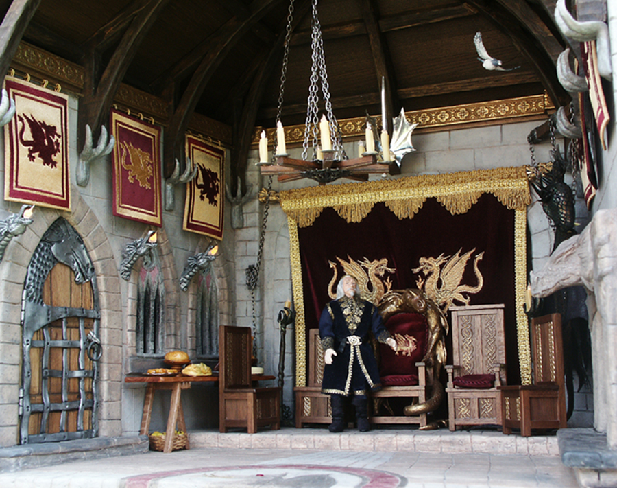 medieval room with hanging chandelier and dragon torches lit